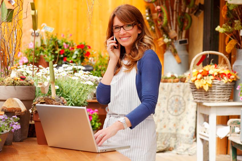 Smiling Mature Woman Florist Small Business Flower Shop Owner. Shallow Focus.