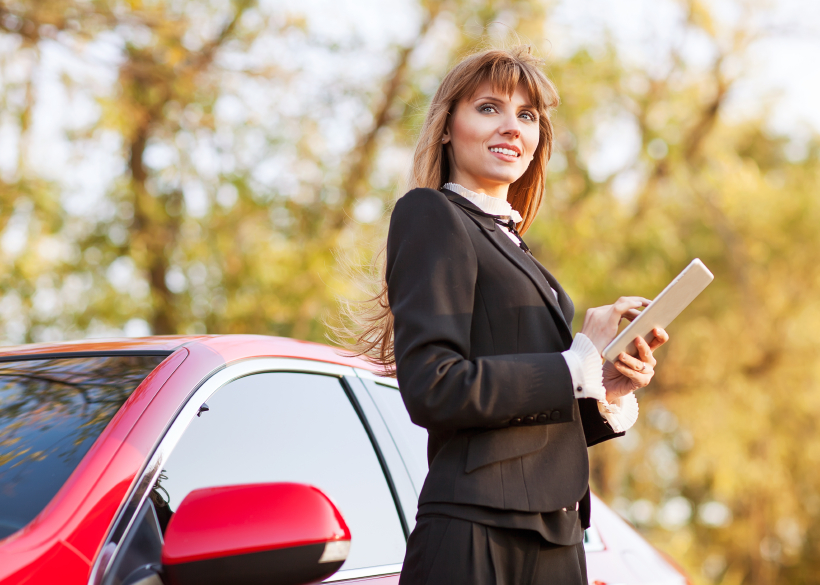 Businesswoman working on digital tablet while standing near the car outdoor