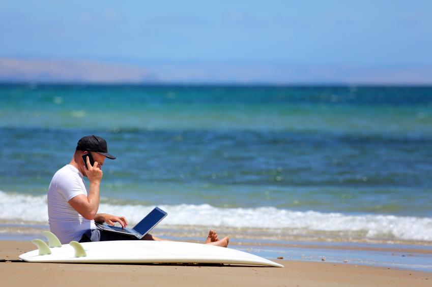 Small business owner working on his laptop at the beach.